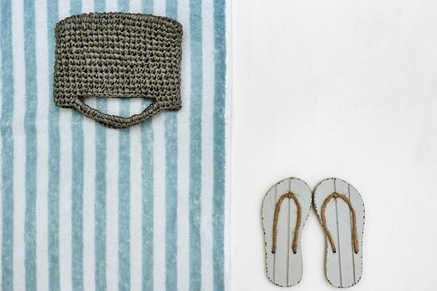 ニットビーチバッグとコピースペースと白い背景の灰色のフリップフロップ。ビーチタオルの縞模様。ビーチでの休暇の概念。