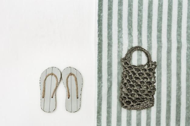ニットビーチバッグとコピースペース付き白地にグレーのビーチサンダル。ビーチタオルの縞模様。ビーチでの休暇の概念。