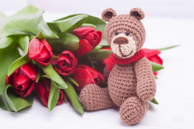 Knitted bear. festive decor. delicate red tulips. valentine's day. handmade, knitted toy, amigurumi