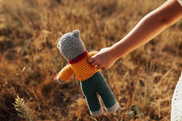 夏のフィールドで小さな女の子の手に編まれたクマ
