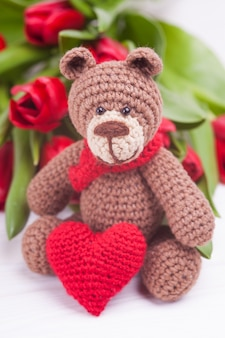 Knitted bear and red tulips bouquet