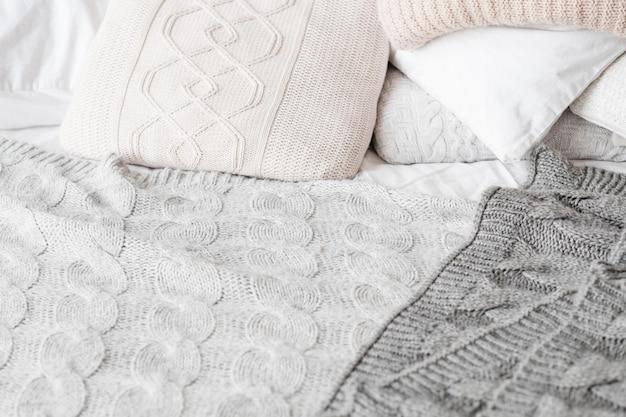 Постельное белье вязаное. уют в спальне. фон подушки и одеяла.