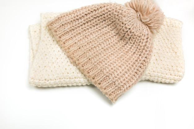 ニットベージュの帽子と白い背景で隔離のスカーフ