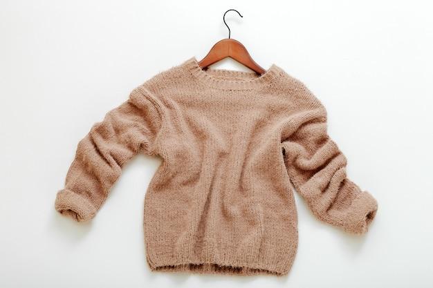 옷걸이에 니트 베이지색 스웨터. 캐시미어 스웨터는 흰색 배경에 평평하게 놓여 있습니다. 따뜻하고 세련된 가정복 겨울 복장 갈색 따뜻한 니트 스웨터 상위 뷰.