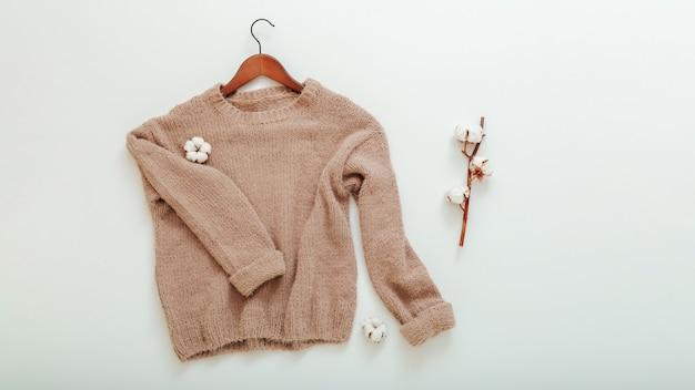 면 꽃이 달린 옷걸이에 베이지색 니트 스웨터. 면 스웨터는 흰색 바탕에 나뭇가지 면으로 날아갑니다. 따뜻하고 세련된 가정복 겨울 복장 갈색 따뜻한 니트 스웨터 상위 뷰. 긴 웹 배너입니다.