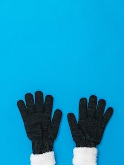 ニット黒の女性の手袋の下の青い背景。希望と出会いのコンセプト。ファッションレディースアクセサリー。