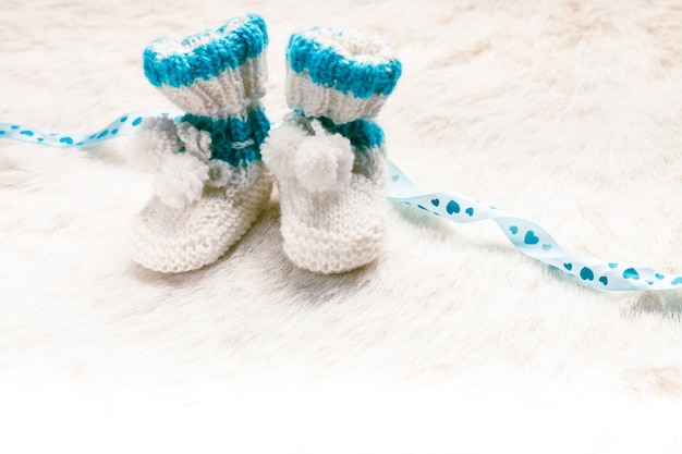 Knitted blue baby booties for little boy with copy space