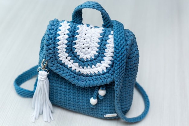 Вязаный синий рюкзак на белом фоне