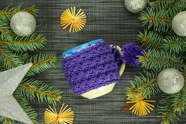 ニットの青いマグカップ、ボール、モミの枝。クリスマスと新年のコンセプト。