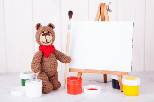Knitted brown bear with brush and paint near the easel. handwork, creativity. amigurumi. postcard