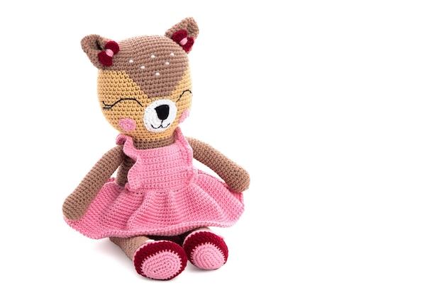 Вязаная игрушка кошка в розовом платье и туфлях сидит на белой поверхности