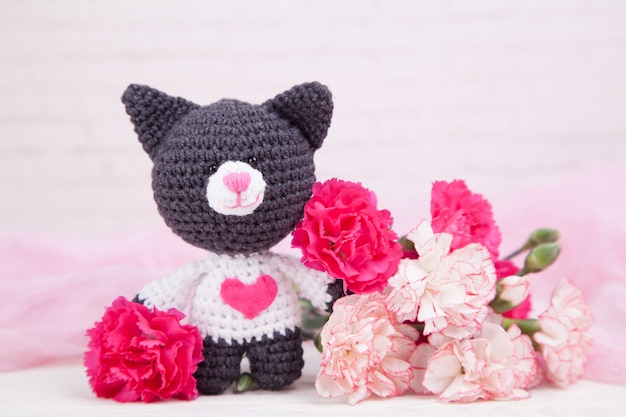 마음으로 니트 고양이. 성 발렌타인의 날 장식. 니트 장난감, 아미 구루미. 발렌타인 데이 인사말 카드.