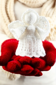 女性の手で編まれたクリスマスの天使、クローズアップ