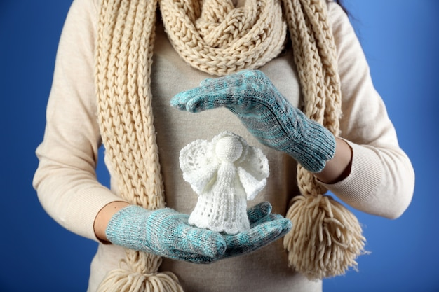 色の背景に女性の手で編まれたクリスマスの天使