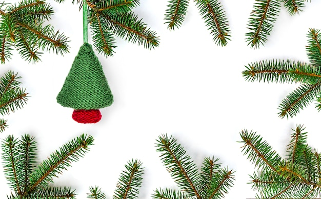 Knitted christmas tree in frame of fir branches on new year background