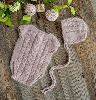 木製のテーブルの上に新生児のためのニット服の構成。かわいいスーツと帽子の淡いピンク色で設定された幼児のウールの服のデザイン
