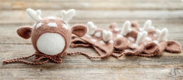 木製のテーブルの上に新生児のためのニット服の構成。幼児の羊毛の帽子のデザインセット