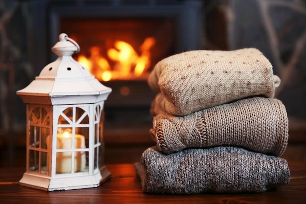 暖炉の背景のテーブルの上のニット服