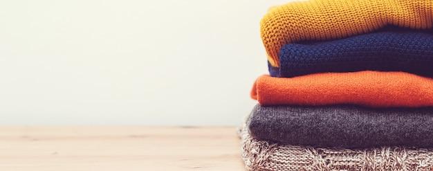 ニットカラーの洋服、ヴィンテージスタイル。テーブルの上のセーターの山。秋冬シーズンのニットウェア。