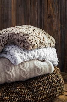 나무 벽에 누워 니트 아늑한 스웨터