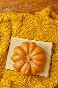 Вязаный уютный свитер с открытой книгой и тыквой на деревянном фоне романтическая композиция вид сверху осень ...