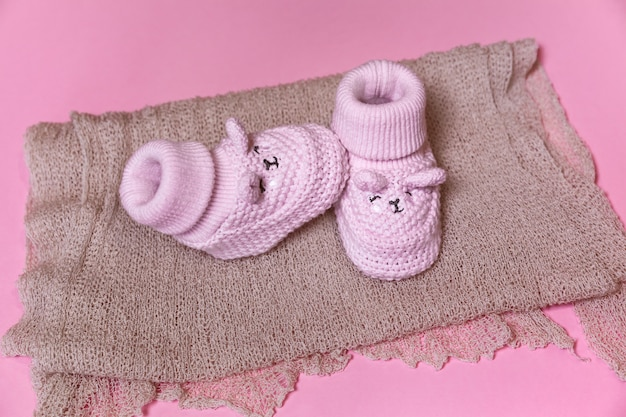 Knitted crochet newborn shoes on a pink background waiting for a baby girl