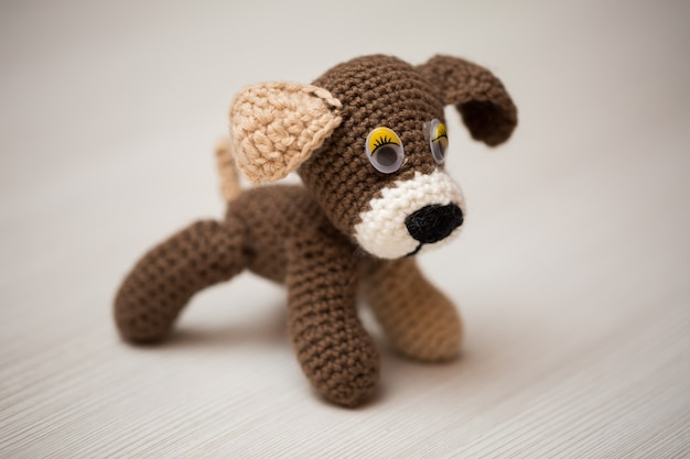 Knitted dog hand on wooden table