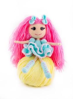 ピンクの髪と毛糸のボールで編まれた人形