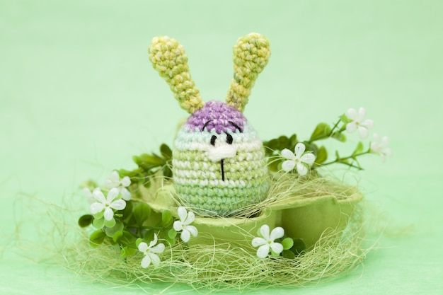 Knitted easter decor eggs, flowers , bunny on a green background, amigurumi