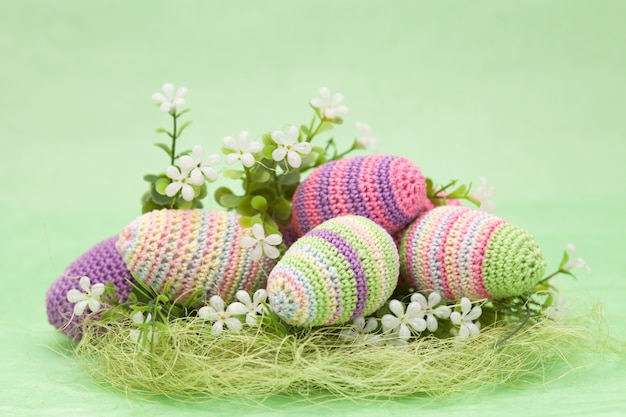 Knitted easter decor eggs, flowers on a green background, handmade