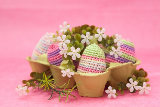 Knitted easter decor eggs, flowers on a pink background, handmade