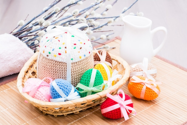 Knitted easter eggs and cake in a basket, jug and willow