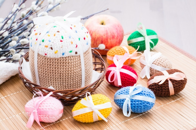 Knitted easter eggs and cake in a basket and willow on a wooden table