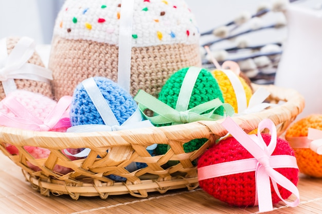 Knitted easter eggs and easter cake in a basket on a wooden table. easter still life