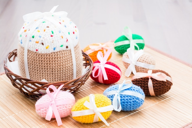 Knitted easter eggs and easter cake in a wicker basket on a wooden table
