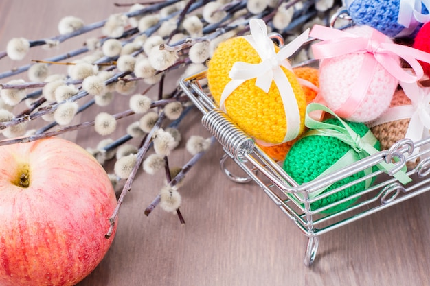 Knitted easter eggs tied with colored ribbons in a metal basket, an apple and willow on a wooden table