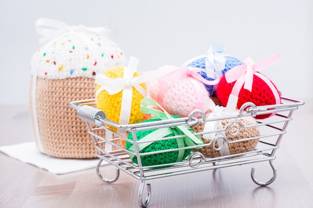Knitted easter eggs tied with colored ribbons in a metal basket and easter cake on a wooden table
