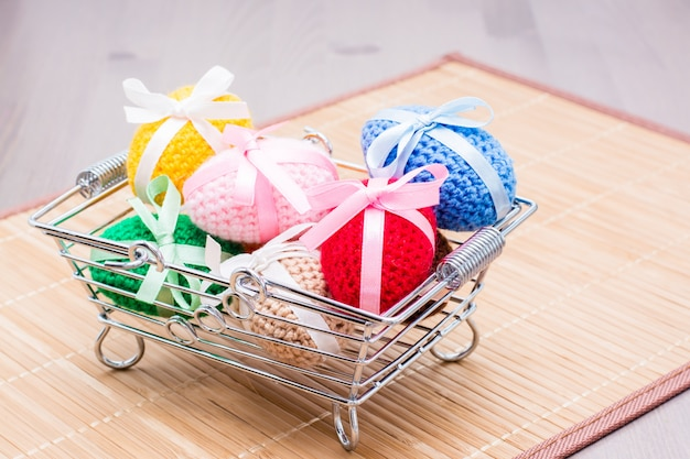 Knitted easter eggs tied with colored ribbons in a metal basket on a napkin on the table