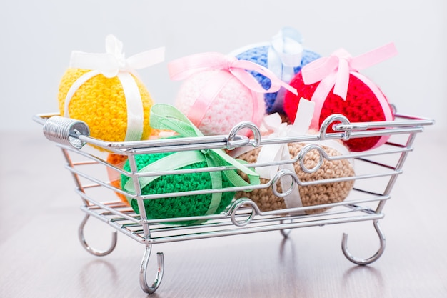 Knitted easter eggs tied with colored ribbons in a metal basket on a wooden table