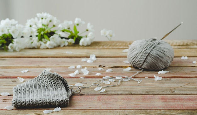 Knitted fabric on wooden background with white flowers