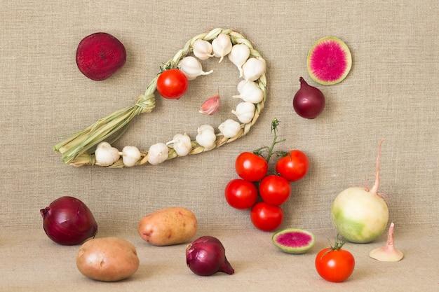 ニットニンニク、スライス大根、タマネギ、小枝の赤いトマト、黄麻布の背景にジャガイモ