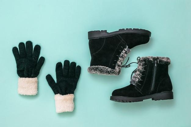 Вязаные перчатки и зимние женские сапоги на синем фоне. модные стильные женские зимние сапоги. плоская планировка.