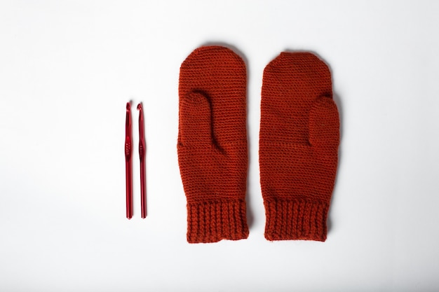 Knitted gloves in red on a white background
