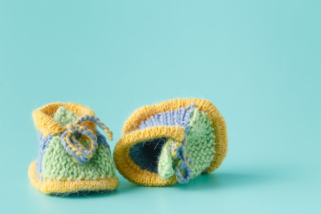 Knitted green baby booties for little boy