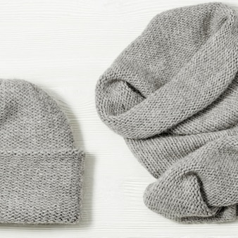 Knitted grey hat and scarf on white wood background. fashionable warm clothes for girl or woman.