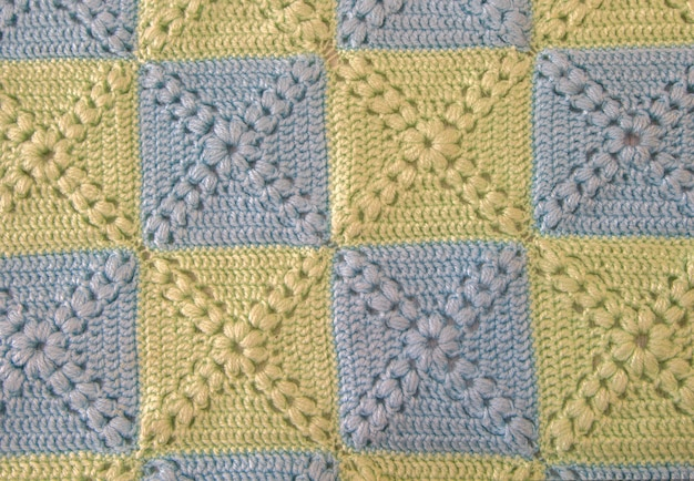 Knitted handmade colourful blankets, rustic crochet stitches gentle colors.