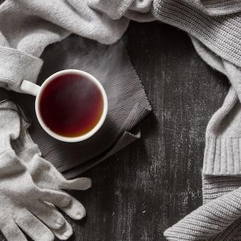 니트 수제 울 의류. 가을 또는 겨울 옷과 검은 색 표면에 뜨거운 차 한잔.