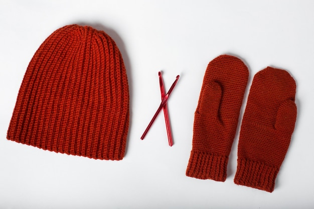 Knitted hat with gloves red on a white background