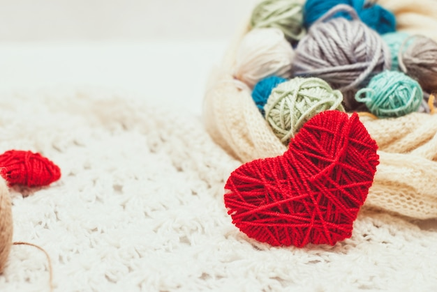 Knitted heart symbol and balls of yarn