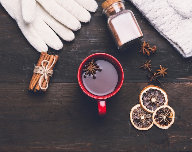 Knitted mittens and red cup with a drink on brown wooden table, top view